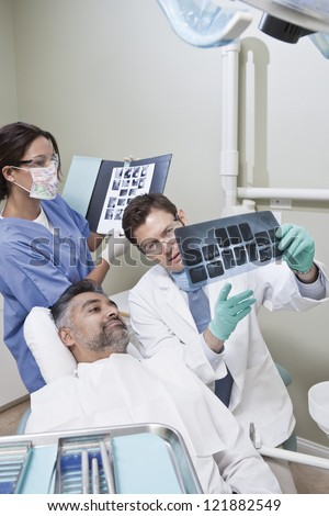 Nurse with male dentist explaining patient his x-ray reports in clinic - stock photo