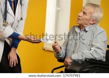 Nurse woman giving client card to senior man in wheelchair  - stock photo