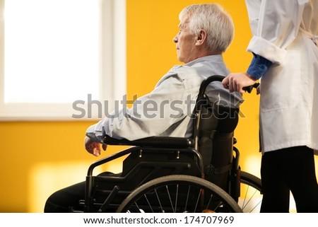Nurse woman with senior man in wheelchair  - stock photo
