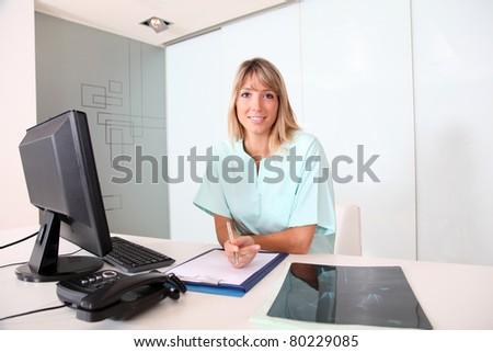 Nurse working on desktop computer in office - stock photo