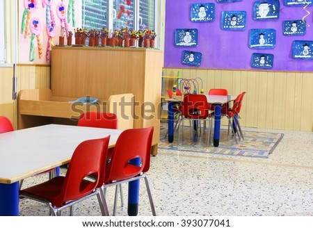 Nursery class with small red chairs and children's drawings on the walls