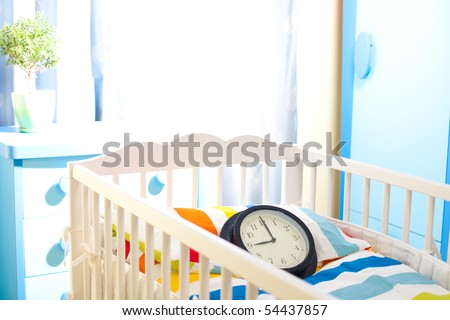 Nursery room with baby bed and clock counting time for new owner - stock photo