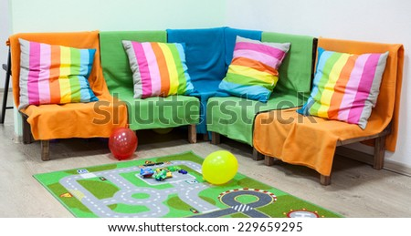 Nursery room with bright sofa, toys and balloons on the floor - stock photo