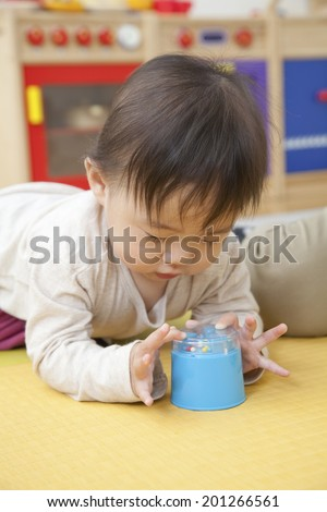 Nursery school children playing with toys - stock photo