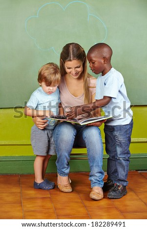 Nursery teacher and children reading a book together in kindergarten - stock photo
