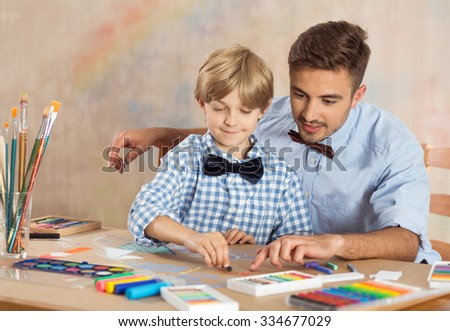 Nursery teacher and little child drawing picture