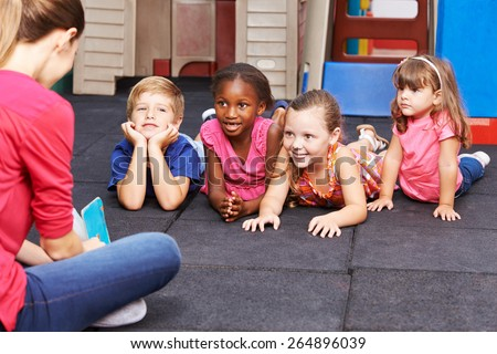 Nursery teacher reading story book to group of kids in kindergarten - stock photo
