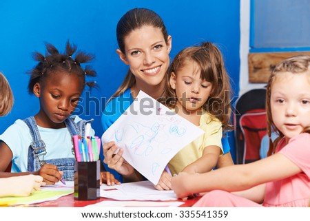 Nursery teacher with many children showing a drawing in kindergarten - stock photo