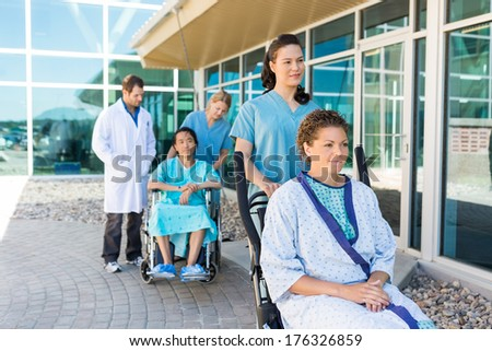 Nurses assisting patients on wheelchairs with doctor standing outside hospital building - stock photo