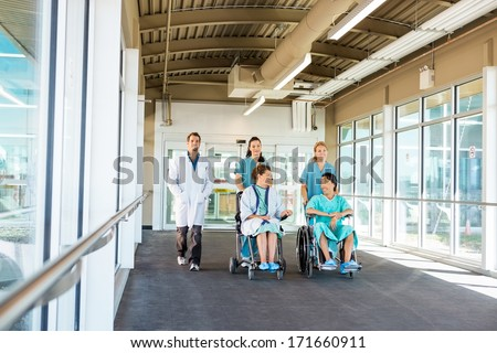 Nurses pushing patients on wheelchairs while walking with doctor at corridor in hospital - stock photo