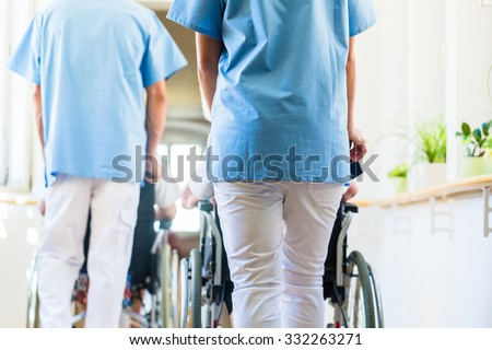 Nurses pushing seniors in wheelchair thru nursing home - stock photo