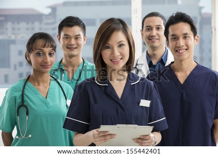 Nurses standing in a hospital with her team in background. Multi-ethnic team of caucasian, Chinese and indian medical staff. - stock photo