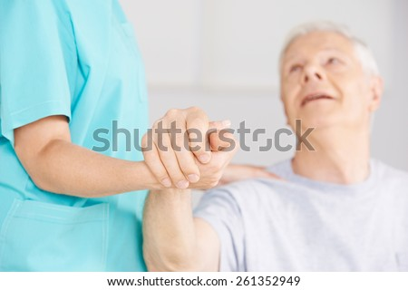 Nursing assistant holding hand of senior man for support - stock photo