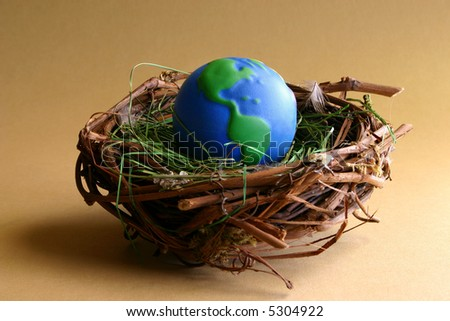Nurturing Earth:  A soft globe sits protected in a bird's nest. - stock photo