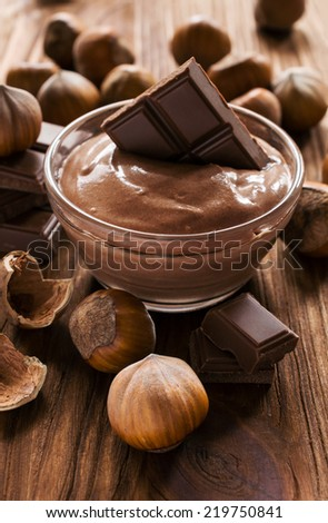 nut butter , hazelnut and chocolate on wooden background - stock photo