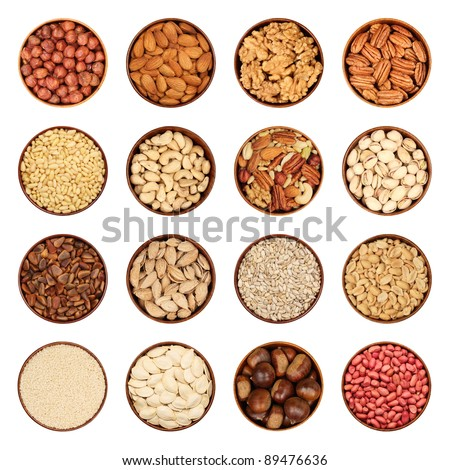 Nut mix - hazelnuts, peeled almonds, walnuts, pecans, pine nuts, cashews, nut mix, pistachios, seeds, pumpkin seeds, chestnuts, peanuts, sesame seeds in wooden bowls, isolated, background white. - stock photo