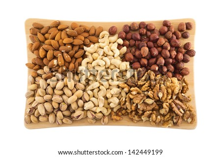 Nut mix of peanut, hazelnut, walnut, almond and pistachio over the wooden cutting board isolated over white background - stock photo