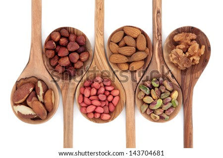 Nut selection in olive wood spoons over white background. - stock photo
