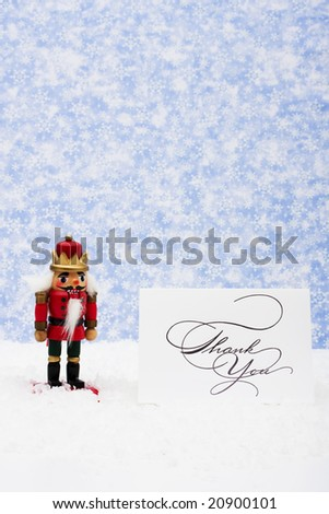 Nutcracker sitting on snow with thank you card on a snowflake background, nutcracker - stock photo