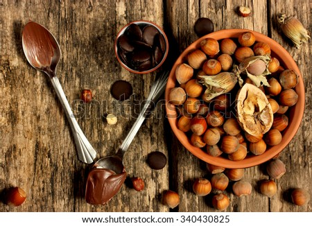 Nutella, chocolate and hazelnuts on a wooden background - stock photo