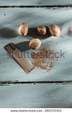 nutmeg and grater on a wooden background - stock photo