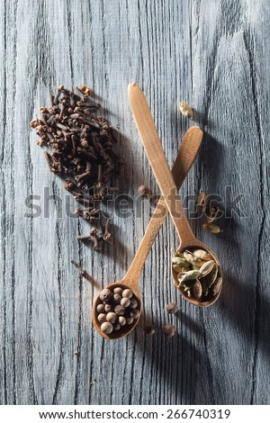 Nutmeg, clove and allspice in old spoon on wooden background with long shadows dramatic contrast light - stock photo