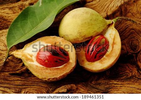 nutmeg fruits on wooden background - stock photo