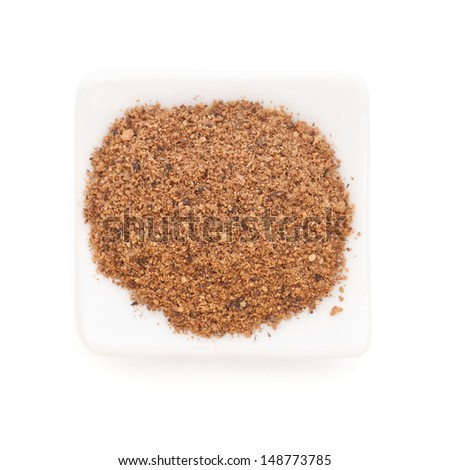 Nutmeg powder (Myristica fragrans) in a white bowl on white background. Used as a spice in many sweet as well as savoury dishes and medicine. - stock photo