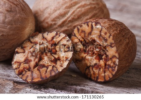 Nutmeg sectional close-up on an old wooden table - stock photo