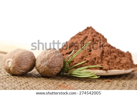 nutmeg with a sprig of rosemary and cacao powder in the wooden spoon on sacking base - stock photo