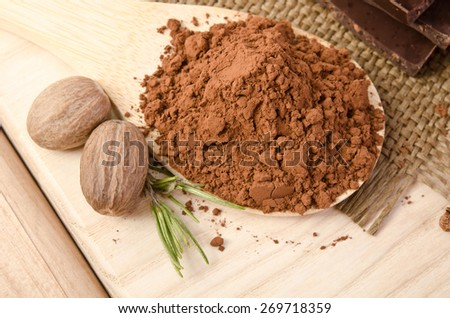 nutmeg with a sprig of rosemary and cacao powder in the wooden spoon on wooden table - stock photo