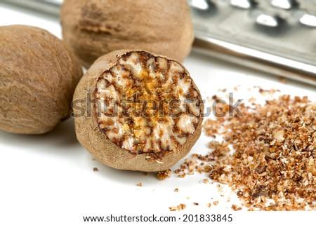 nutmeg with grinder isolated on white - stock photo
