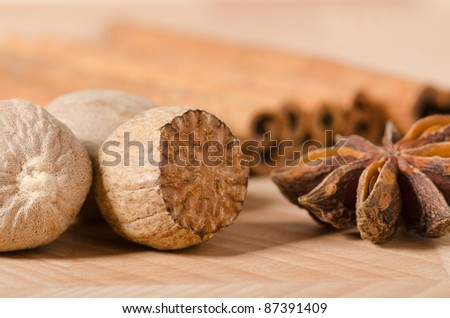 Nutmegs and star anise with cinnamon sticks in the background