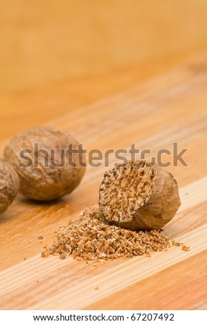 Nutmegs whole and grind over wood background - stock photo