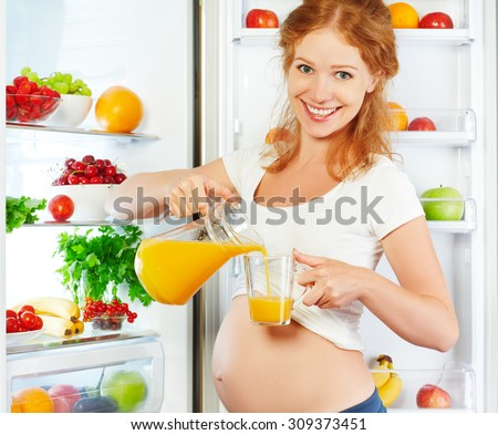 nutrition and diet during pregnancy. Pregnant woman standing near refrigerator with with orange juise - stock photo