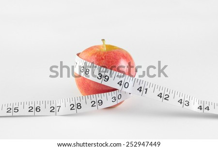 Nutrition and healthy diet concept with apple and measuring tape - stock photo