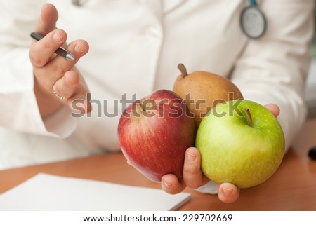 Nutritionist doctor holding fruits and explaining. - stock photo