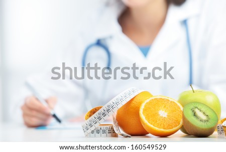 Nutritionist Doctor is writing a prescription. Focus on fruit - stock photo