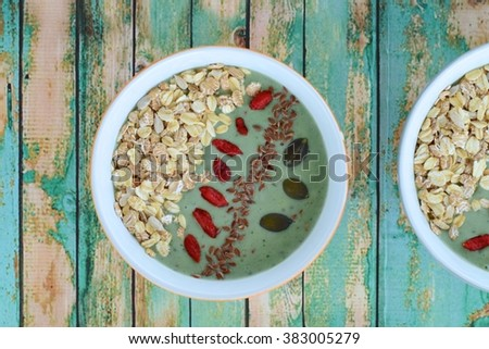 Nutritious green smoothie bowl with goji berries, oats, pumpkin seeds, sunflower seeds  and flax seeds on green wood background. Top view - stock photo