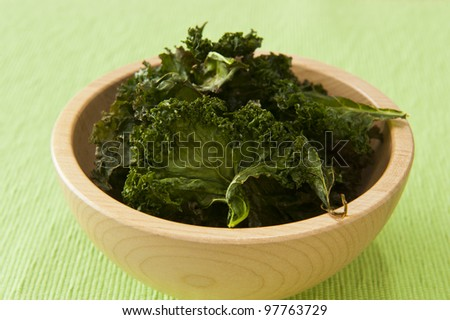 Nutritious snack of roasted kale chips - stock photo