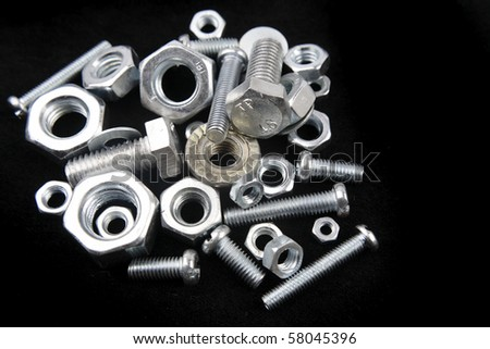 Nuts and bolts on black - stock photo