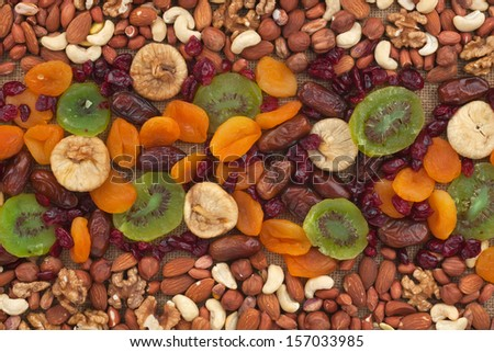 Nuts and dried fruits are on burlap, as background - stock photo