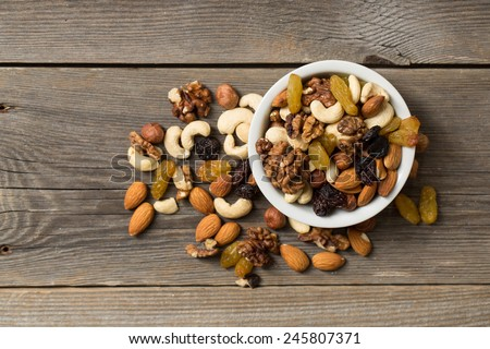 Nuts and dried fruits in a white bowl on a wooden table. View from above.