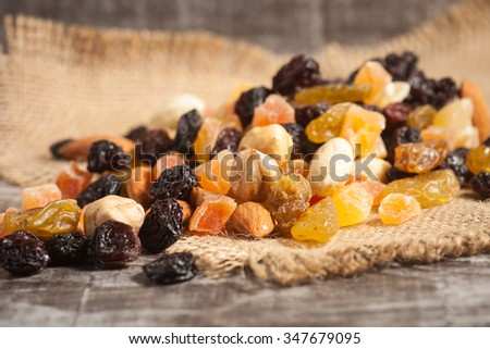 Nuts and dried fruits mix on a rustic sack and wooden background