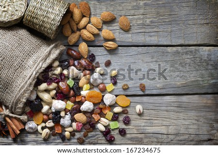 Nuts and dried fruits on vintage wooden boards still life - stock photo