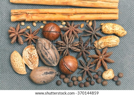 nuts and spices - cinnamon sticks, pecans, almonds, macadamia, peanuts, star anise, black allspice, grains of sesame seeds. The concept of food and ingredients. The view from the top. - stock photo