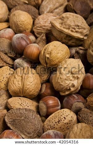 Nuts assortment background (walnuts, hazelnuts, chestnuts, almonds). - stock photo