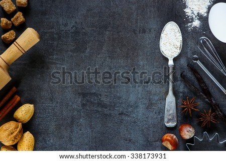 Nuts, flour in vintage spoon, rolling pin and aromatic spices for baking on dark metal background with space for text.. Christmas and holidays concept. Top view. Healthy food ingredients. - stock photo