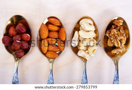 Nuts in spoon on white wooden table with clipping path - stock photo