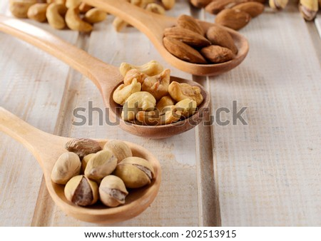 Nuts in the wooden ladle.Selective focus on the cashew nuts in the ladle  - stock photo